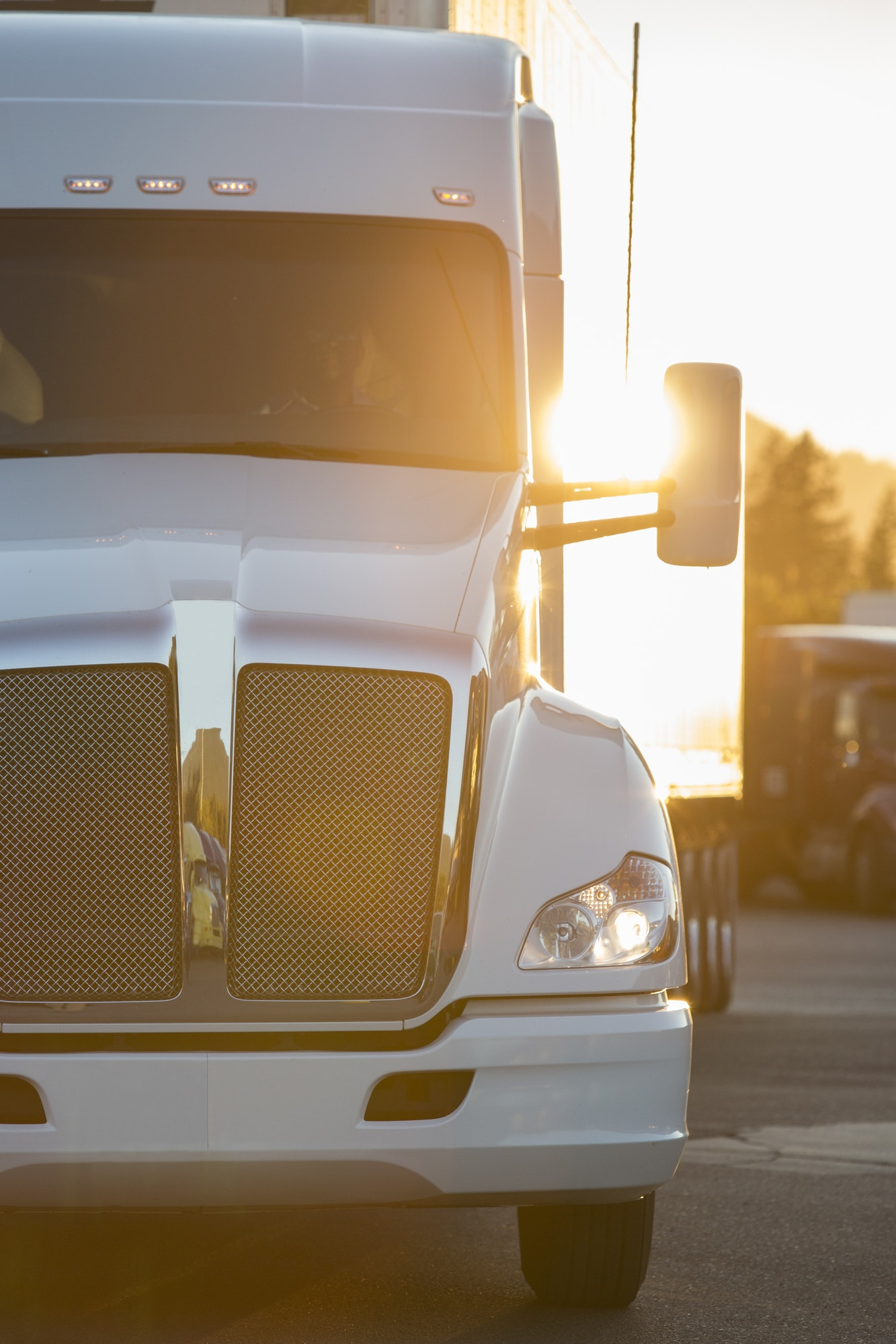 A large commercial truck moving through a truck stop parking lot at sunset.